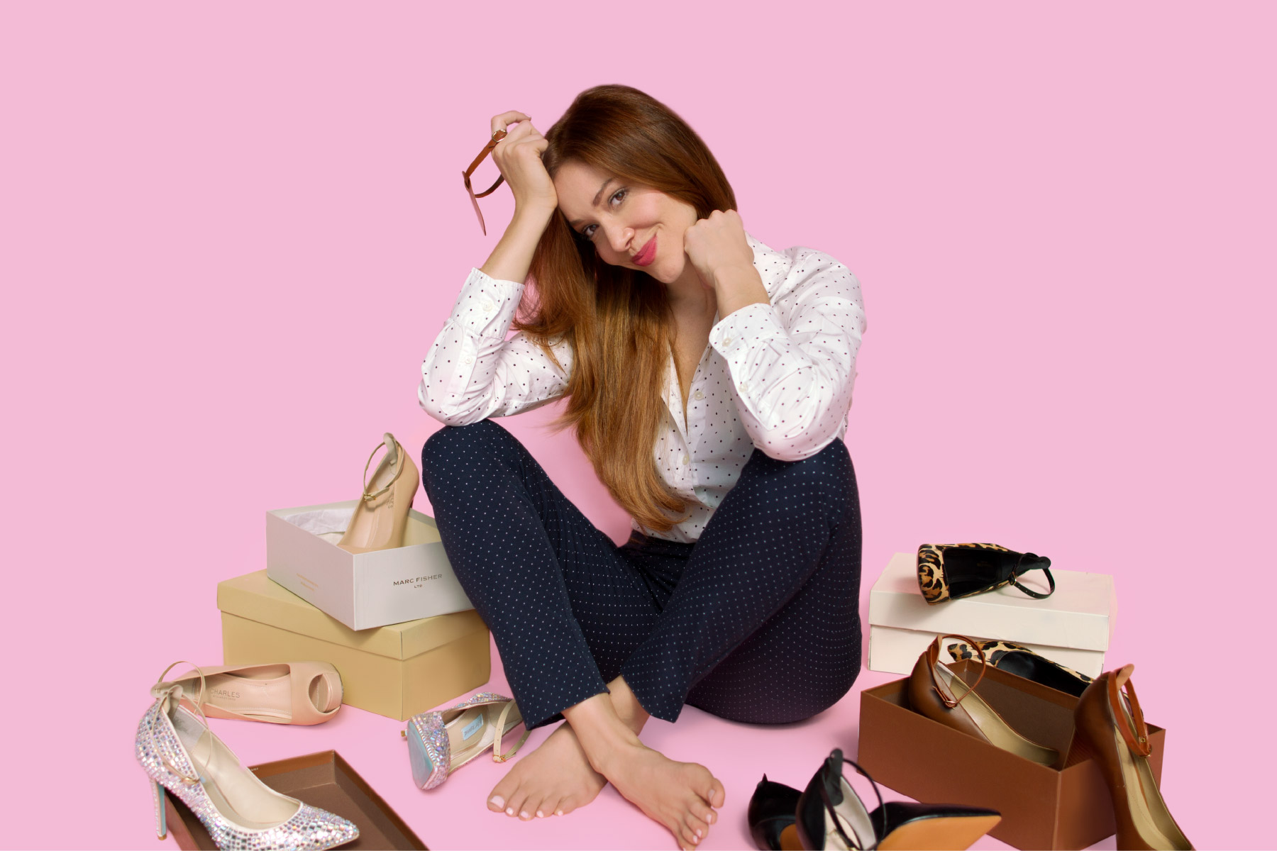 Happy fashionista next to scattered high heels
